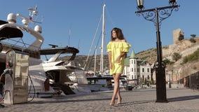 Den unga kvinnan i en klänning och på höga häl promenerar stranden i ultrarapid stock video