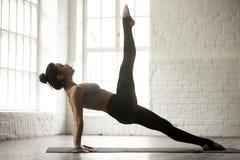 Den unga kvinnan i en lagd benen på ryggen uppåtriktad planka poserar, vindstudion Royaltyfria Foton