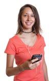 Den unga kvinnan i en röd skjorta älskar musik Royaltyfri Bild