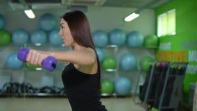 Den unga kvinnan i en sportig likformig är förlovad med en hantel i en idrottshall arkivfilmer