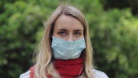 Den unga kvinnan i en steril maskering som ser SAD in i kameraanseendet i, parkerar på trädbakgrunden H?st eller stock video