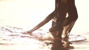 Den unga kvinnan i en svart klänning går i vattnet på stranden lager videofilmer