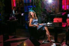 Den unga kvinnan i en turkosklänning sitter i en nattklubb och ett drinkkaffe royaltyfri bild