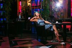 Den unga kvinnan i en turkosklänning sitter i en nattklubb och ett drinkkaffe royaltyfria bilder