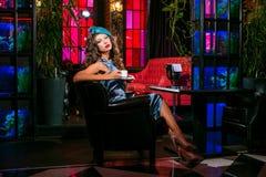 Den unga kvinnan i en turkosklänning sitter i en nattklubb och ett drinkkaffe fotografering för bildbyråer
