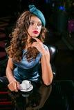 Den unga kvinnan i en turkosklänning sitter i en nattklubb och ett drinkkaffe arkivfoto