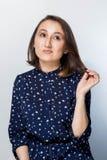 Den unga kvinnan i ett fundersamt poserar och att tänka av alternativen Stående av den tvivelaktigtt seende härliga unga brunette Arkivfoton