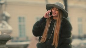 Den unga kvinnan i ett ljust solljus använder hennes telefonleendesamtal i telefonen stock video