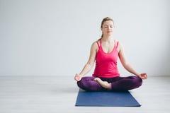 Den unga kvinnan i ett vitt rum som gör yoga, övar Royaltyfri Bild
