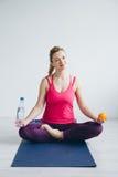 Den unga kvinnan i ett vitt rum som gör yoga, övar Royaltyfria Foton