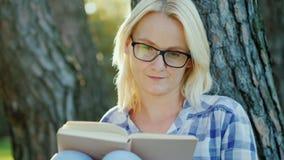 Den unga kvinnan i exponeringsglas läser en bok i parkera Sitter nära ett träd, härligt ljus för solnedgång royaltyfria bilder