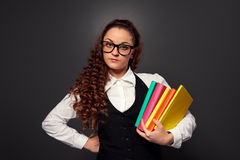 Den unga kvinnan i exponeringsglas med högen av bokar Royaltyfri Foto