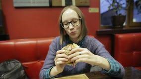 Den unga kvinnan i exponeringsglas som äter snabbmat, hamburgaren och fransman, steker i kafé Attraktivt studentflickasammanträde stock video