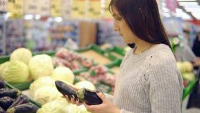 Den unga kvinnan i grönsakavdelningen av en supermarket väljer aubergine arkivfilmer