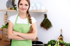 Den unga kvinnan i grönt förkläde går för att laga mat i ett kök Hemmafrun smakar soppan vid träskeden royaltyfri foto