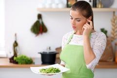 Den unga kvinnan i grönt förkläde lagar mat i ett kök Hemmafrun erbjuder ny sallad arkivfoto