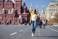 Den unga kvinnan i gult lag går på den röda fyrkanten i Moskva Arkivfoton