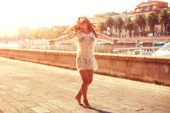 Den unga kvinnan i hatt och gullig sommar klär snurr på vägen, med fridsamt stadlandskap som ser solnedgång Arkivfoto