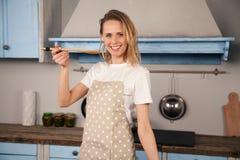 Den unga kvinnan i hennes kök smakar en maträtt som hon har lagat mat och att le royaltyfri bild