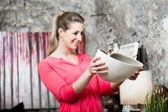 Den unga kvinnan i inre shoppar intresserat i lampa arkivbild