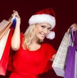 Den unga kvinnan i jul cap paper paket för händer Royaltyfri Fotografi