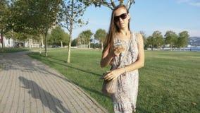 Den unga kvinnan i klänning drar ut från den smarta telefonen för handväskan och startar samtal lager videofilmer