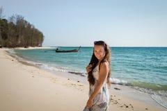 Den unga kvinnan i klänning går på stranden på kusten av havet royaltyfria bilder