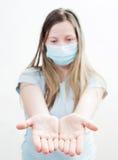 Den unga kvinnan i läkarundersökning maskerar. Arkivfoto