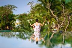 Den unga kvinnan i lotusblomma poserar reflekterat i vattnet Arkivfoton