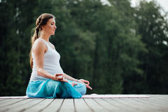 Den unga kvinnan i lotusblommapositionen är praktiserande yoga i skogen bredvid floden sitta på mats träpir Royaltyfria Bilder