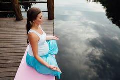 Den unga kvinnan i lotusblommapositionen är praktiserande yoga i skogen bredvid floden sitta på mats träpir Arkivfoton