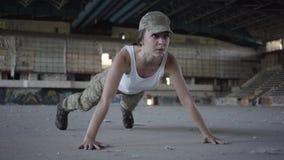 Den unga kvinnan i militär likformig vrider om ut från golvet på ett konkret golv i en övergiven byggnad En kvinna utbildar arkivfilmer