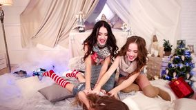 Den unga kvinnan i nytt år, flickor som skrattar för att ha gyckel, systrar spelar nära julgranen arkivfilmer