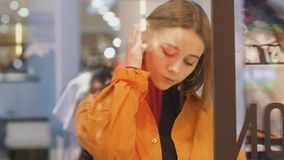 Den unga kvinnan i orange skjortablick till och med shoppar exponeringsglas arkivfilmer