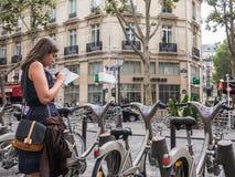 Den unga kvinnan i prickklänning läser översikten med Velib cyklar, Pari Royaltyfria Foton