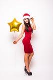 den unga kvinnan i röd klänning och santa julhatt med den guld- stjärnan formade att le för ballong Arkivfoto