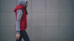 Den unga kvinnan i rött sleeveless omslag går bredvid den gråa väggen av byggnad arkivfilmer