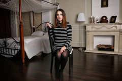 Den unga kvinnan i randig klänning sitter på aChair bland lyxigt sovrum Arkivbild