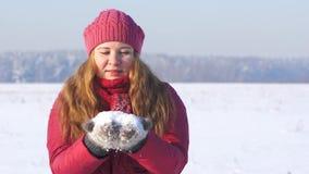 Den unga kvinnan i rosa färger beklär att blåsa på snö stock video