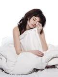 Den unga kvinnan i sänguppvaknande tröttade sömnlöshethangov Royaltyfri Fotografi