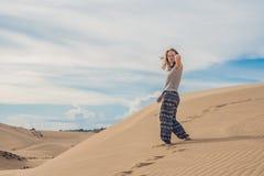 Den unga kvinnan i sandig öken går bara mot molnig himmel för solnedgången arkivfoton