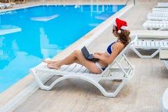 Den unga kvinnan i Santa Claus hattarbete på bärbara datorn vid pölen, jul semestrar i ett tropiskt land Frilans- arbete för kvin arkivfoto