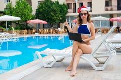 Den unga kvinnan i Santa Claus hattarbete på bärbara datorn vid pölen, jul semestrar i ett tropiskt land Frilans- arbete för kvin arkivfoton