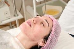 Den unga kvinnan i skönhetsalong gör applikation av att fukta, uppmjukning som regenererar maskeringen royaltyfria foton