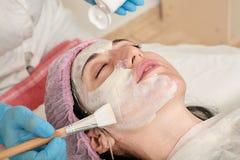 Den unga kvinnan i skönhetsalong gör applikation av att fukta, uppmjukning som regenererar maskeringen arkivfoto