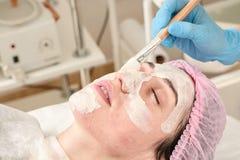 Den unga kvinnan i skönhetsalong gör applikation av att fukta, uppmjukning som regenererar maskeringen royaltyfri bild