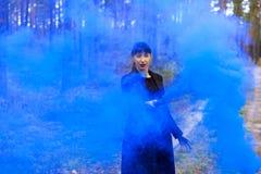 Den unga kvinnan i skogen som har gyckel med den blåa rökgranaten, bombarderar Royaltyfri Bild