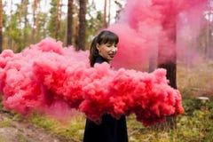 Den unga kvinnan i skogen som har gyckel med den röda rökgranaten, bombarderar Royaltyfri Fotografi