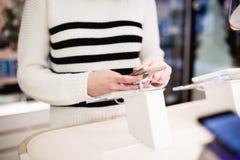 Den unga kvinnan i smart telefon shoppar royaltyfria bilder