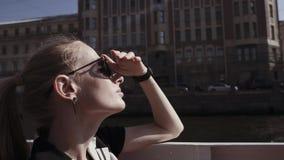 Den unga kvinnan i solglasögon går för ett fartyg till och med flodkanalen lager videofilmer